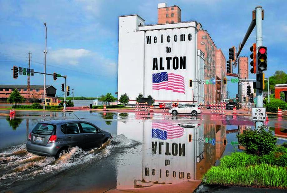 A vehicle drives through Mississippi River flood water in downtown Alton, on Monday. Flooding from the Mississippi River closed streets in downtown, forced the closure of Argosy Casino and flooded the basements of several businesses. The Mississippi River is expected to crest at 34.8 feet later on Monday, almost 14 feet above flood stage. The red painted line beneath the American flag on the grain silos denotes the height of flood water in 1993. Photo: David Carson | St. Louis Post-Dispatch Via AP
