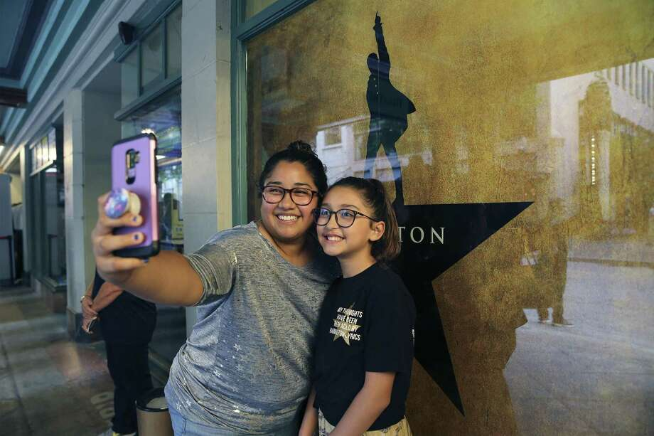 "Iris Beca and her 12-year-old daughter, Alyssa, take a selfie in front of a ""Hamilton"" poster before joining a long line of people filtering into the Majestic Theater for the opening of the show ""Hamilton"" on Tuesday, May 7, 2019. The sold out show will be showing at the Majestic for three weeks. Beca said they had seen the show in Houston and since then she and Alyssa have been hooked on the wildly popular performance. (Kin Man Hui/San Antonio Express-News) Photo: Kin Man Hui, Staff / Staff Photographer / ©2019 San Antonio Express-News"