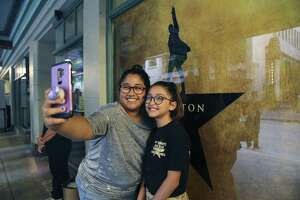 "Iris Beca and her 12-year-old daughter, Alyssa, take a selfie in front of a ""Hamilton"" poster before joining a long line of people filtering into the Majestic Theater for the opening of the show ""Hamilton"" on Tuesday, May 7, 2019. The sold out show will be showing at the Majestic for three weeks. Beca said they had seen the show in Houston and since then she and Alyssa have been hooked on the wildly popular performance. (Kin Man Hui/San Antonio Express-News)"