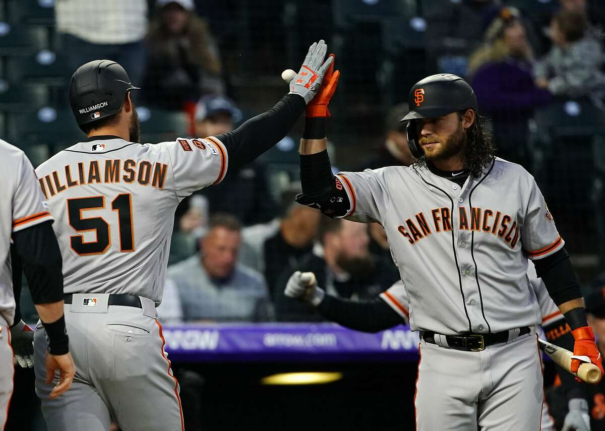 San Francisco Giants' Mac Williamson high-fives Brandon Crawford (35) after hitting a three-run home run against the Colorado Rockies during the fourth inning of a baseball game, Tuesday, May 7, 2019, in Denver. (AP Photo/Jack Dempsey)