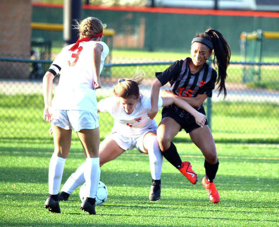 Edwardsville's Katrina Agustin, right, battles for the ball with Alton's Alaina Nasello, middle, and Grace Kane during the first half of Tuesday's game at EHS. Photo: Scott Marion | For The Telegraph