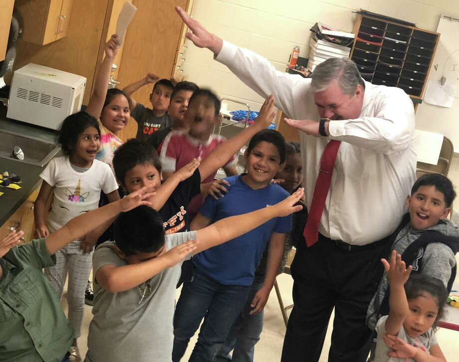 Cleveland ISD Superintendent Chris Trotter, still in his dress shirt, pants and tie, entertains children at Southside Elementary school in Cleveland after the students and staff were trapped by flood waters outside of the school on Tuesday evening. Photo: Submitted