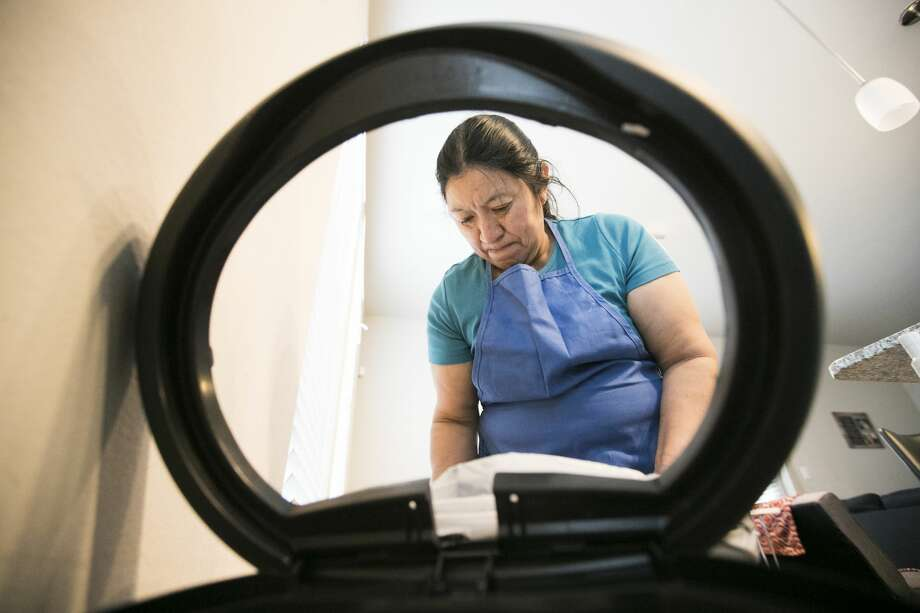 Domestic worker Julia De Leon places a new bag in a trash can for one of her clients in Houston. Photo: Marie D. De Jesús/Staff Photographer