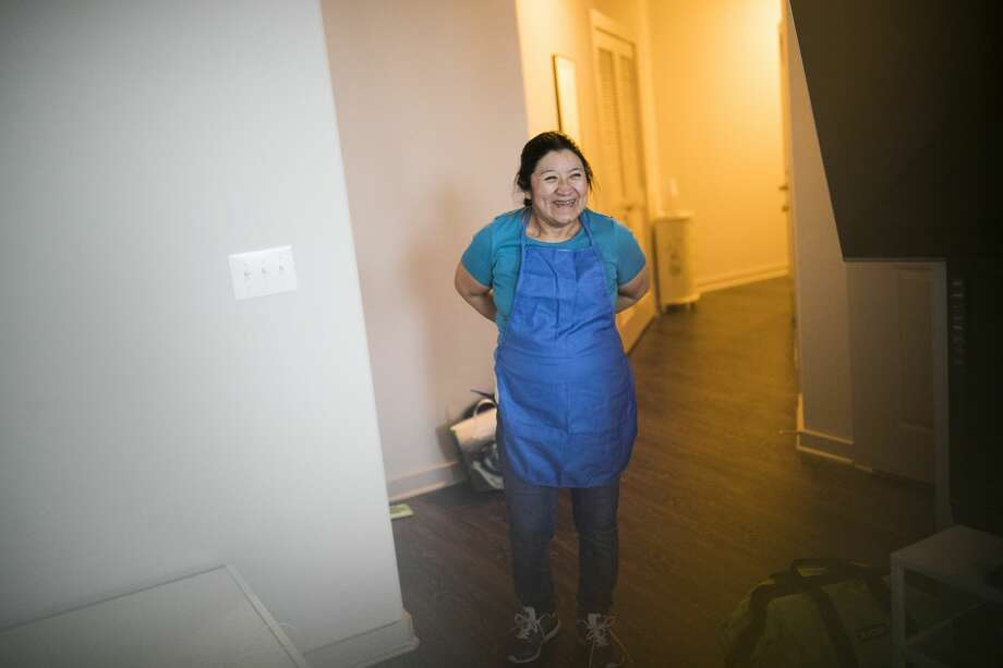 Julia De Leon, a domestic worker puts on an apron as she arrives to a client's apartment to clean up. Photo: Marie D. De Jesús/Staff Photographer