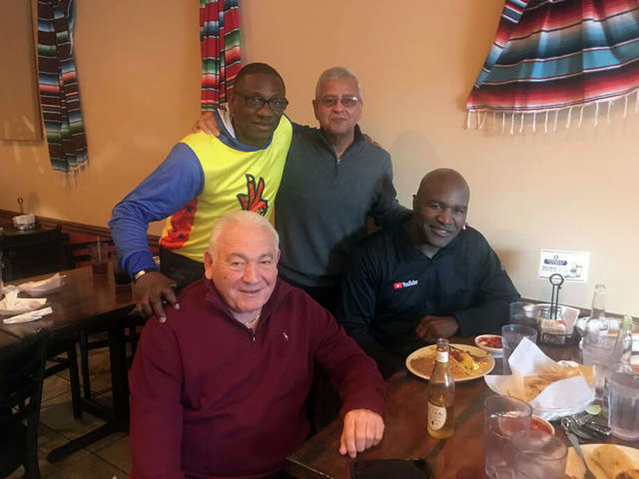 Paul Bogosian sits beside Evander Holyfield with Mike Cross and Bobby Galvan at Chava's Mexican Restaurant during a Taco Crawl late last month in Edwardsville. Photo: Courtesy Of Bobby Galvan