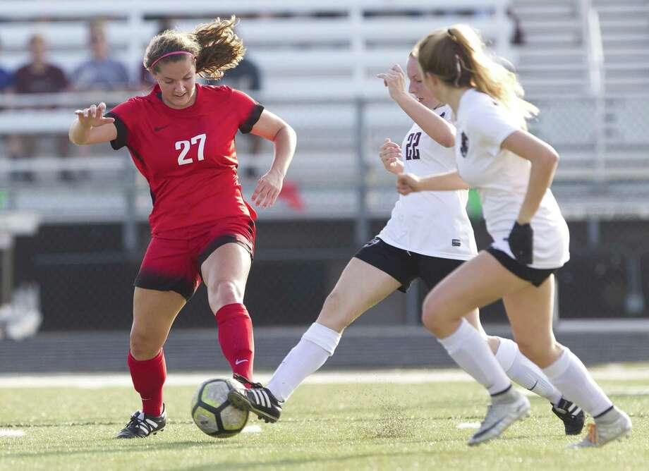 The Woodlands defender Peyton Graves (27) challenges the ball against Round Rock midfielder Tatiana Jerman (22) during the first period of a Region II-6A quarterfinal high school soccer playoff match at Bastrop Memorial Stadium, Friday, April 5, 2019, in Cedar Creek. Photo: Jason Fochtman, Houston Chronicle / Staff Photographer / © 2019 Houston Chronicle