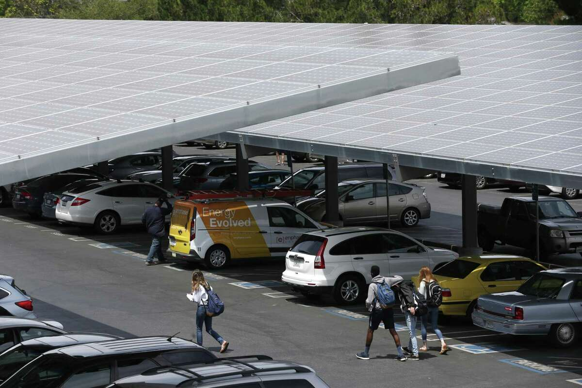 CPS Energy program has announced a community solar program that involves installing solar panels as roofs for covered parking in outdoor lots. The panels will generate electricity for residents who want to use solar power but live in an apartment or rented houses. Shown is a California high school parking lot that uses solar panel arrays as covered parking.