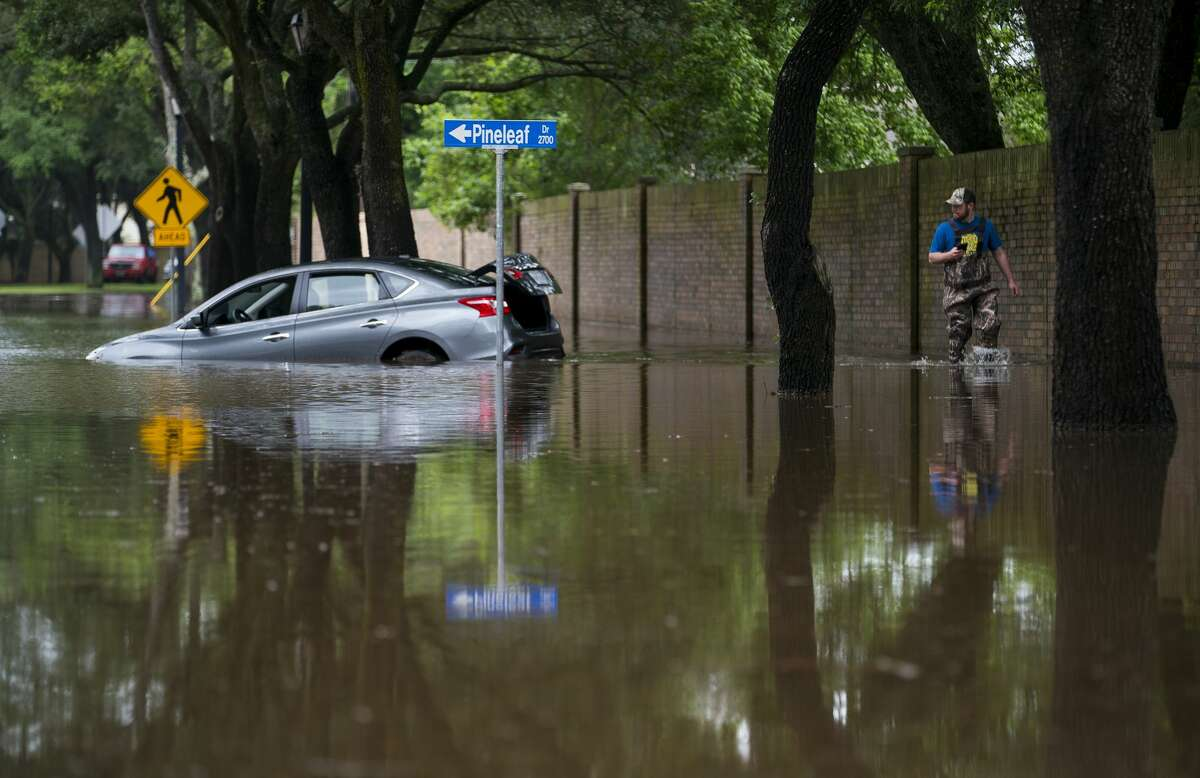 A man walks past a flooded car on Williams Trace Blvd. in Sugar Land, TX, Wednesday, May 8, 2019. The road is closed past Austin Parkway and onto Sweetwater Blvd. after the area was pounded by rain Tuesday.