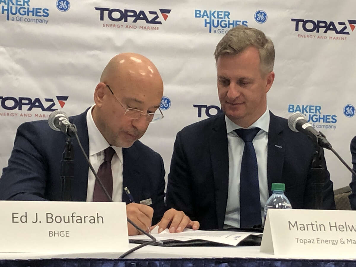 Baker Hughes Vice President Ed Boufarah, left, and Topaz Energy and Marine COO Martin Helweg sign an agreement at the Offshore Technology Conference in Houston. Baker Hughes has entered into a deal to deploy new Internet of Things technology to monitor motor oil and other lubricants on nearly two dozen ships of Topaz's ships based in Dubai.
