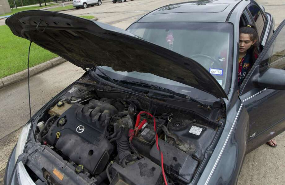 New Caney High School student Nayeli Ramirez waits for her car battery to charge before attempting to start it, Wednesday, May 8, 2019, in New Caney. Ramirez said heavy rains flooded the school's parking lot, forcing her to get a ride home in her boyfriend's truck later that evening. Photo: Jason Fochtman, Houston Chronicle / Staff Photographer / © 2019 Houston Chronicle