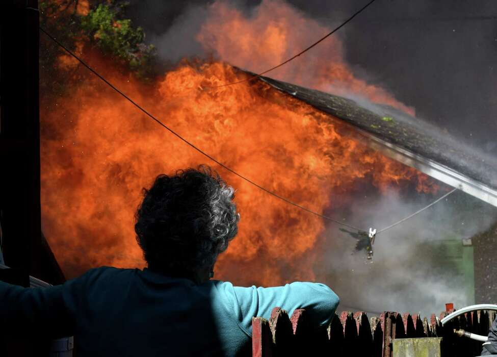 Kathleen DeRosa watches in horror as her backyard garage on Sixth Avenue is consumed by flames from the massive blaze on 5th Avenue that destroyed the Alpha Lanes bowling alley on Wednesday, May 8, 2019, in Troy, N.Y. (Will Waldron/Times Union)