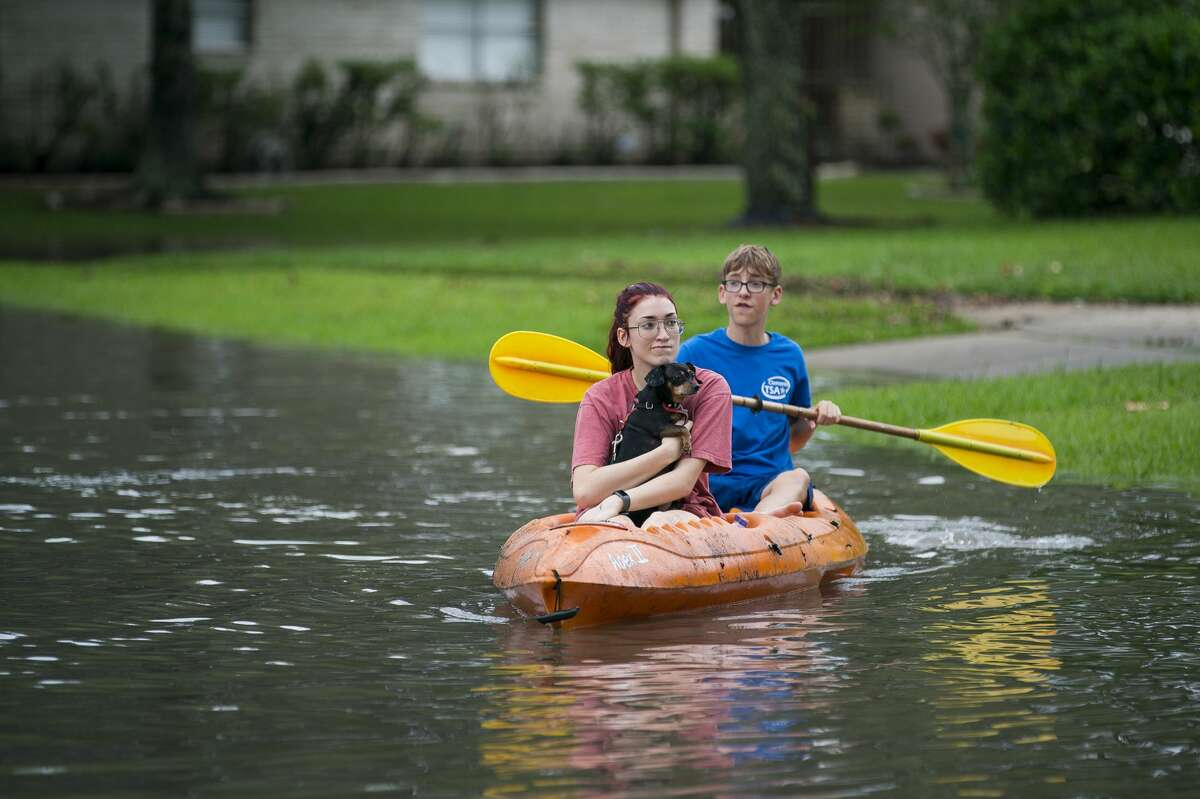 Siblings Katie and Lander Meinen survey their street by kayak with their dog, Bailey, in the Colony Bend neighborhood of Sugar Land, Wednesday, May 8, 2019. Residents have been surprised that the water has not receded more quickly as it has in the past when the rain has stopped. In a video released Wednesday morning, the mayor of Sugar Land told residents that levees to the Brazos River had been closed, and that water was now being pumped over the levees into the Brazos, making the water recede much more slowly. More rain is forecast for the coming days.