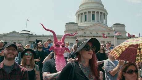 """Satanic Temple supporters at the unveiling of the Baphomet monument on the grounds of the state capitol in Little Rock, Ark., in Penny Lane's """"Hail Satan?"""""""
