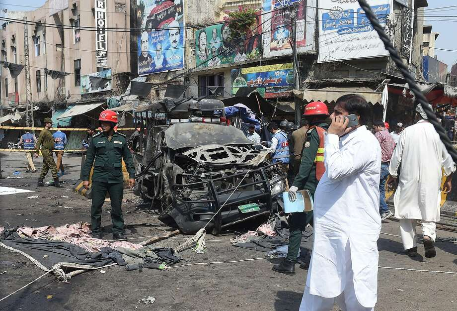 Security officials in Lahore, Pakistan, examine the site of a bombing that broke a lull in militant violence in the nation. Photo: Arif Ali / AFP / Getty Images