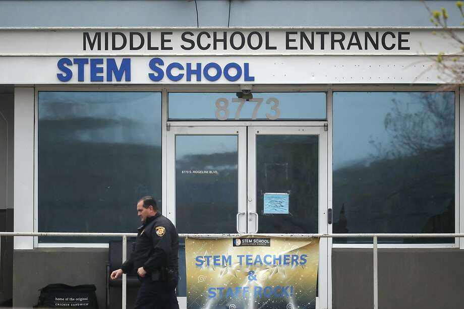 A Douglas County, Colo., Sheriffs Department deputy walks past the doors to the STEM Highlands Ranch school, a day after two students allegedly opened fire on their classmates. Photo: David Zalubowski / Associated Press