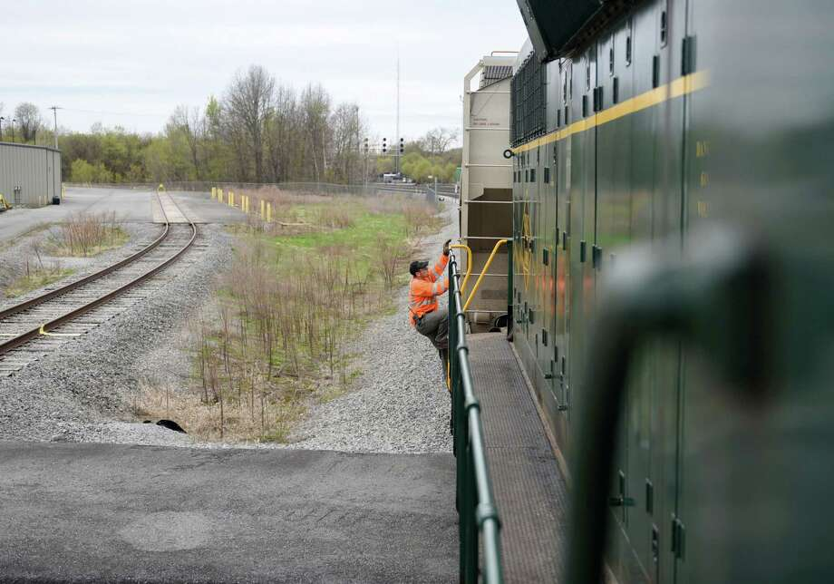 Conductor Edward Scully climbs aboard the locomotive engine on Wednesday, May 1, 2019 at the former PCB processing plant in Fort Edward, NY. (Phoebe Sheehan/Times Union) Photo: Phoebe Sheehan, Albany Times Union / 20046823A