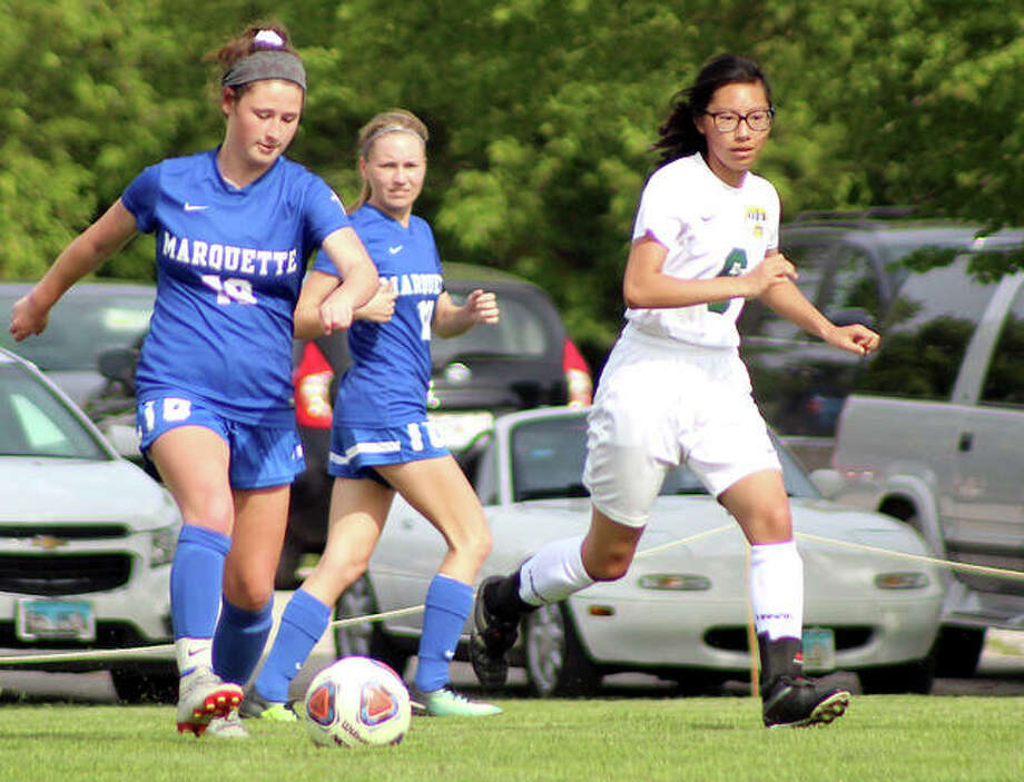 Madelyn Smith of Marquette (18) brings the ball upfield against Metro East East Lutheran's Hannah Ritter (6) Tuesday at Gordon Moore Park. Marquette posted an 8-0 victory Photo: Pete Hayes/For The Intelligencer