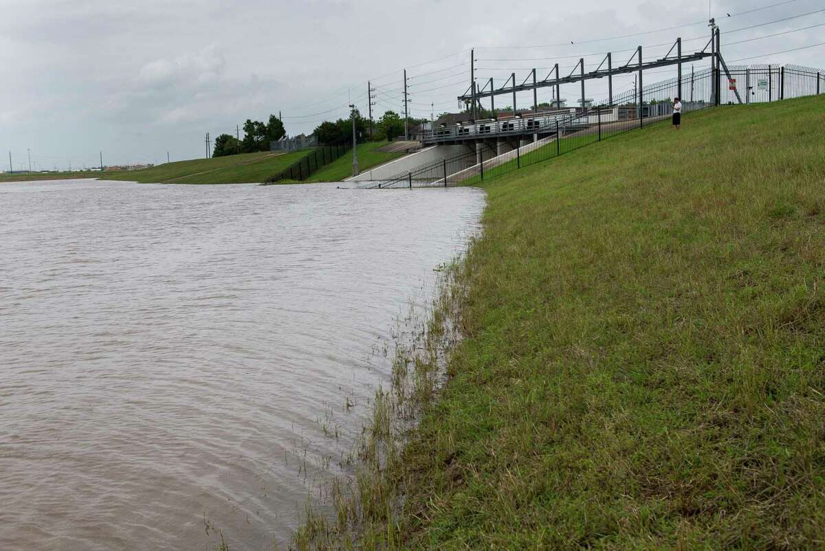 George Cho watches water being pumped out of the First Colony area across the levee near Clements High School in Sugar Land, Wednesday, May 8, 2019. The Fort Bend Levee Improvement District No. 2 said that both of their pump stations are running at full capacity to pump rain water out of the area protected by the levee. The flood gates that protect the levee district from the Brazos River have been closed because of the high level of the Brazos downstream from the ditches that drain the levee district.