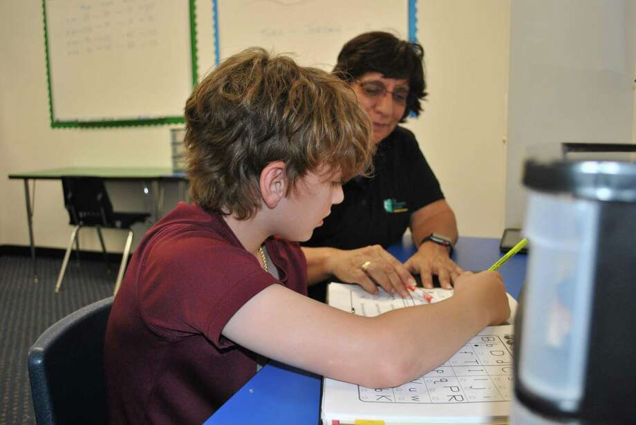Student Johnny Vitale receives a reading lesson from Rita Garcia, the head instructor at The Tutoring Center at 3310 East Broadway in Pearland.