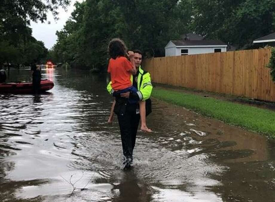 A Spring Firefighter carries a child through a flooded street in Spring, which experienced flash flooding on Tuesday, May 7. Photo: Courtesy Of Spring Fire Department Facebook Page