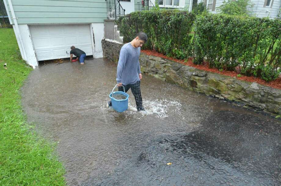 Alan Zurita uses a bucket along with family members and neighbors to try and clear some of the water that has flooded their driveways and garages along Ward St during heavy rains and flooding in Norwalk Conn. on Tuesday September 25, 2018. The city's Department of Public Works is stepping up its efforts to address flooding. Photo: Alex Von Kleydorff / Hearst Connecticut Media / Norwalk Hour