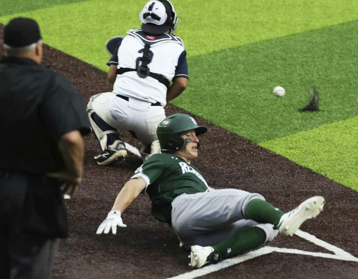 Reagan's Zane Raba slides home for a score against O'Connor catcher Javier Perez in Game 2 of their best-of-3 first-round baseball playoff series at North East Sports Park on Friday, May 3, 2019. Reagan defeated O'Connor, 10-4, to move on to the next round of the playoffs. (Kin Man Hui/San Antonio Express-News)