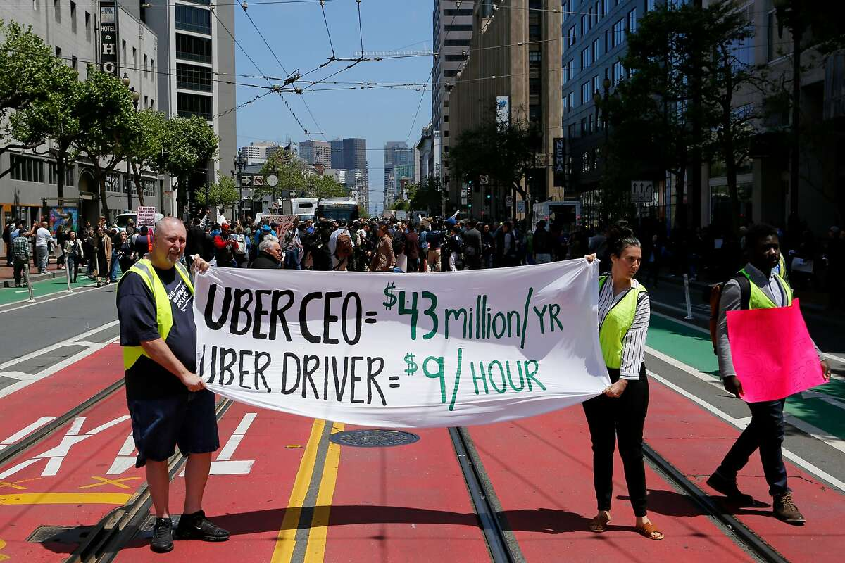 Eddie Wheeler, a former Uber driver, and Sarah Mason, a Lyft driver, protest outside Uber headquarters on Wednesday, May 8, 2019, in San Francisco, Calif.