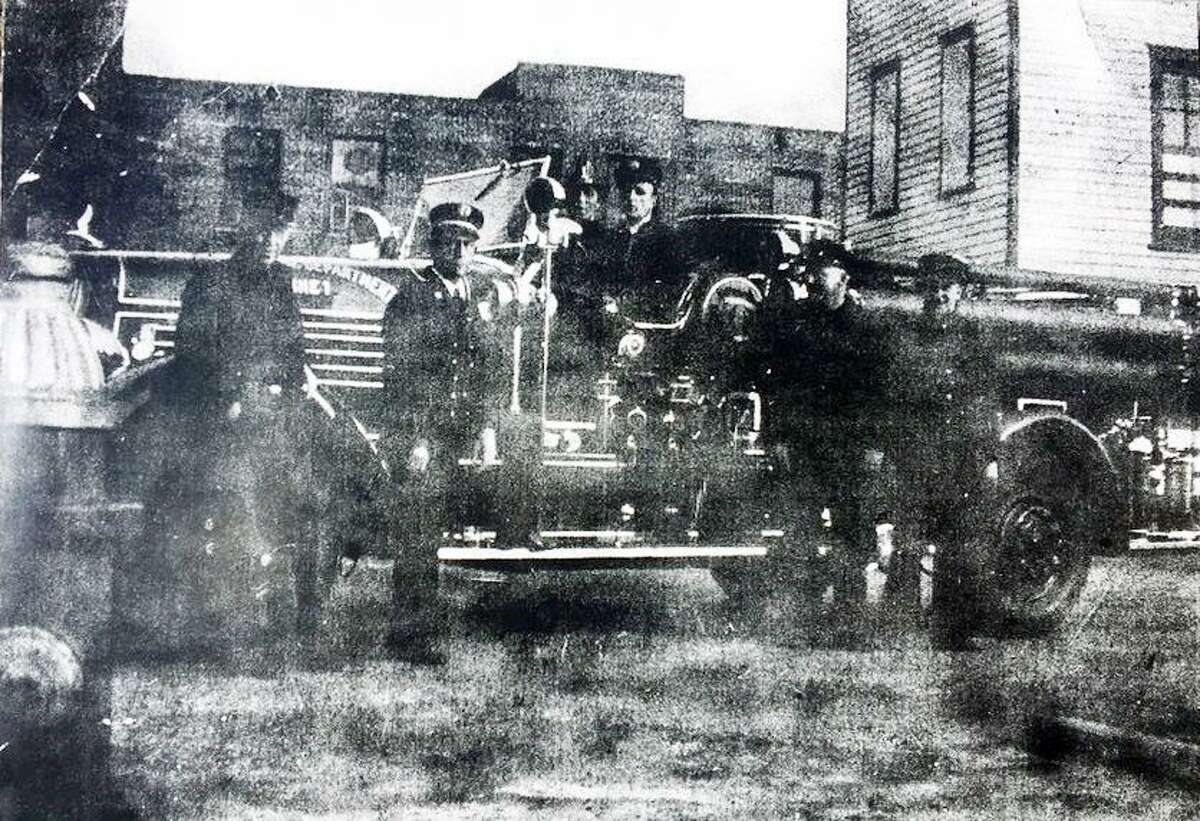 Stamford firefighters gather in front of the Central Fire House likely in the 1940s or '50s. Behind the wheel is Laurence D. Hogan, Sr. with Joe Donahue beside him. Standing are Chief Victor H. Veit, Louis Sandella, Mickey Roberts and Deputy Chief Charles H. Speh.