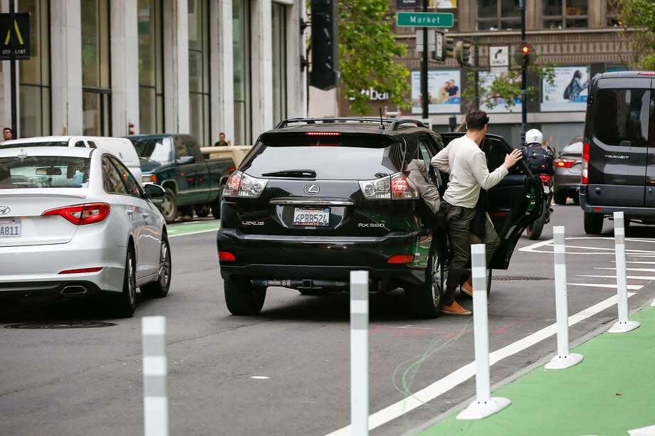 A man exits a double parked rideshare car downtown at 2nd Street and Market Street while cars behind go around on Wednesday, May 8, 2019 in San Francisco, Calif. Photo: Amy Osborne, Special To The Chronicle