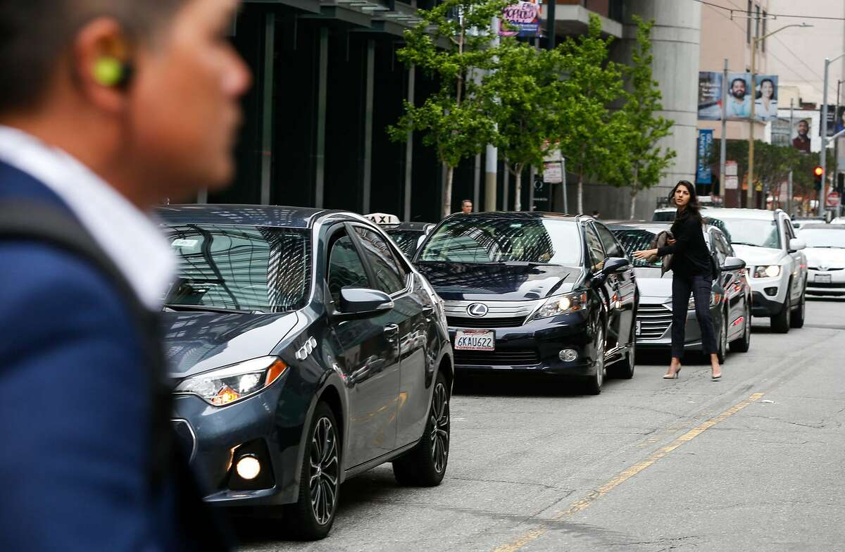 A woman exits a double parked rideshare car downtown at 3rd Street and Market Street on Wednesday, May 8, 2019 in San Francisco, Calif.
