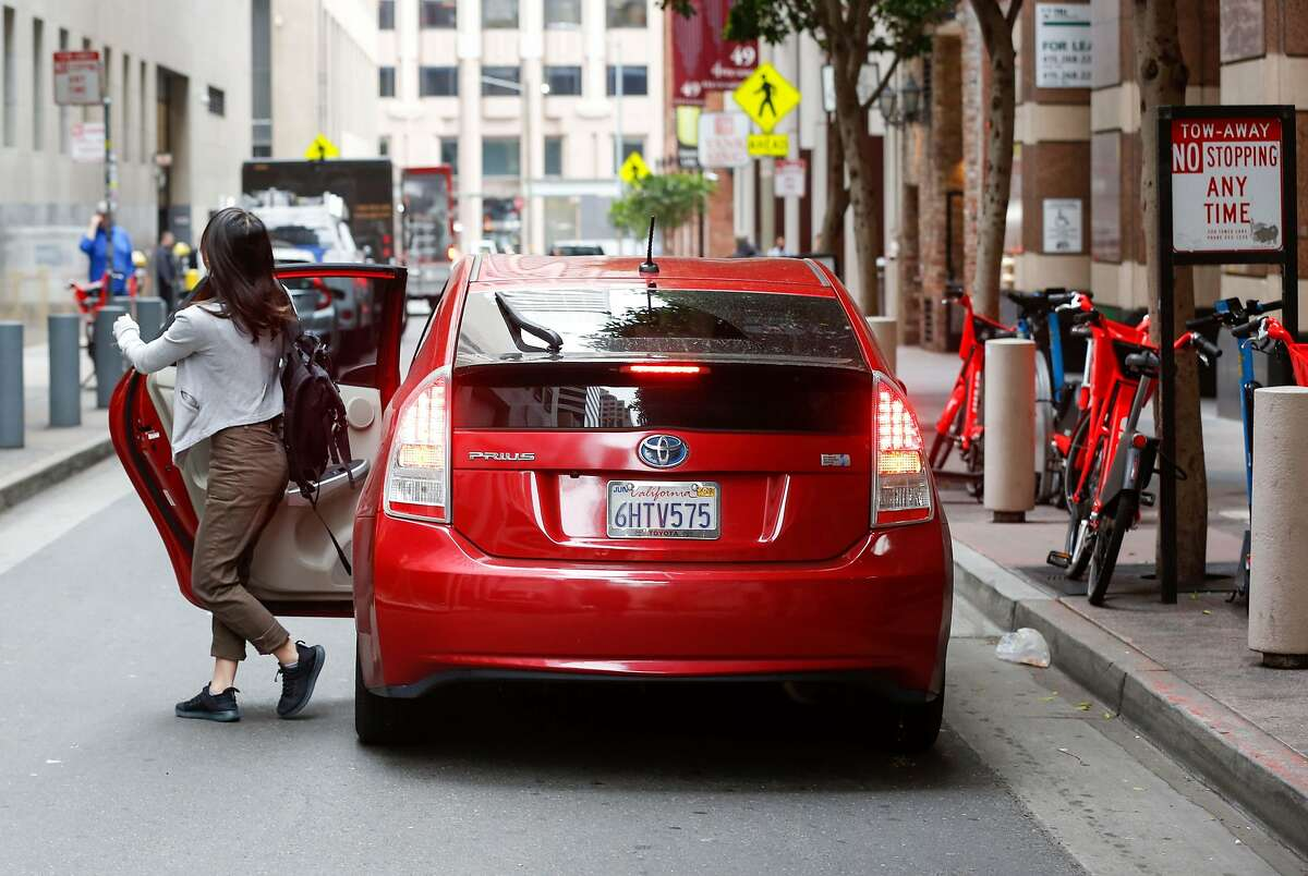 A woman exits a double parked rideshare car downtown on Stevenson Street on Wednesday, May 8, 2019 in San Francisco, Calif.