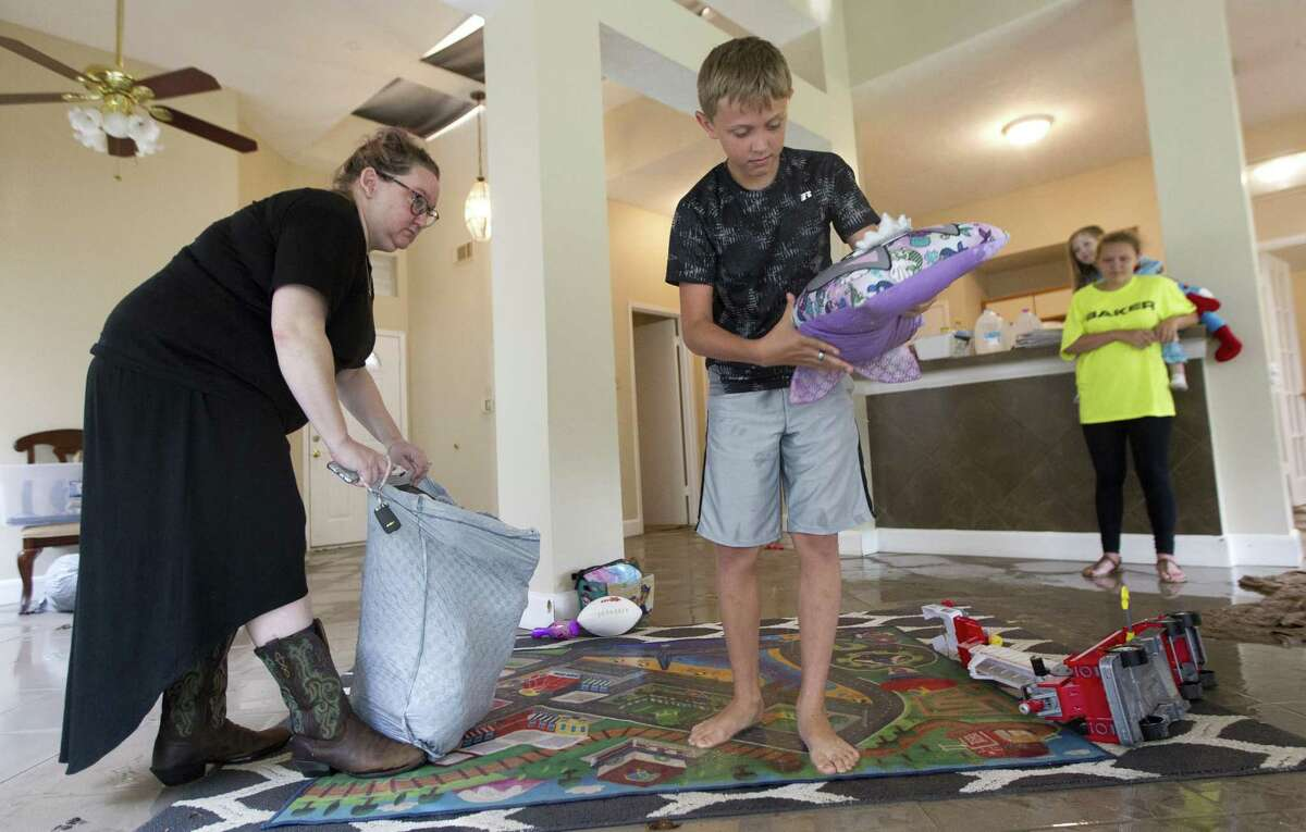 Ryan Cleven wrings out clothes and other items after returning to their home in the Sherwood Trail subdivision, Wednesday, May 8, 2019, in Kingwood, Heavy rain battered parts of southeast Texas prompting flash flood warnings, power outages and calls for water rescues.