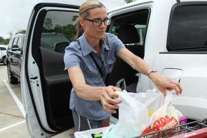 Kingwood resident Heather Baserto, walks out of the H-E-B on West Lake Houston Parkway and loads her truck in Kingwood on May 8, 2019 to prepare for the heavy rainfalls that will come throughout the week.
