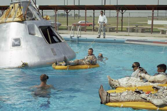 In this June 1966 photo, the prime crew for the first manned Apollo mission practice water egress procedures with full scale boilerplate model of their spacecraft. In the water at right is astronaut Edward H. White (foreground) and astronaut Roger B. Chaffee. In raft near the spacecraft is astronaut Virgil I. Grissom. NASA swimmers are in the water to assist in the practice session that took place at Ellington AFB, near the Manned Spacecraft Center, Houston.