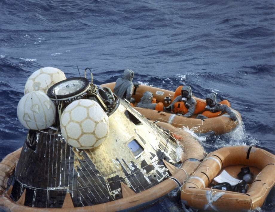 "US Navy pararescueman Lieutenant Clancey Hatleberg disinfects Apollo 11 astronauts Neil Armstrong, Michael Collins, and Edwin ""Buzz"" Aldrin in a life raft during recovery operations on July 24, 1969 at the successful completion of their lunar landing mission. (NASA)"