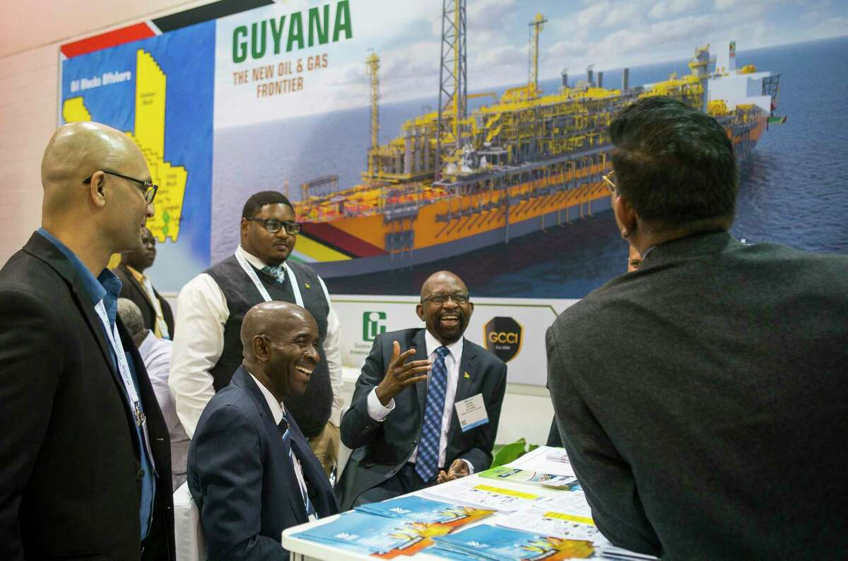 Alex Graham, center, CEO of Tagman Media Inc, laughs while a group talks at the Guyana booth during the annual Offshore Technology Conference inside NRG Arena, Tuesday, May 7, 2019. The conference, which usually takes place every May at NRG Center but was canceled this year, has booked its 2021 conference, though a little later than is typical. The event is scheduled to take place Aug. 16-19, 2021,