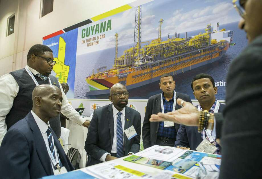 Alex Graham, center, CEO of Tagman Media Inc, listens while a group talks at the Guyana booth during the annual Offshore Technology Conference inside NRG Arena, Tuesday, May 7, 2019. Guyana has a presence at the conference for the first time this year. Photo: Mark Mulligan, Houston Chronicle / Staff Photographer / © 2019 Mark Mulligan / Houston Chronicle