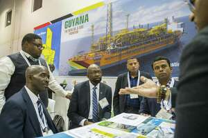 Alex Graham, center, CEO of Tagman Media Inc, listens while a group talks at the Guyana booth during the annual Offshore Technology Conference inside NRG Arena, Tuesday, May 7, 2019. Guyana has a presence at the conference for the first time this year.