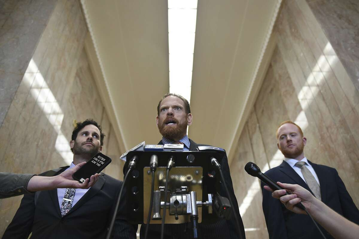 Attorneys Curtis Briggs, center, and Tyler Smith, left, who represent Max Harris, speak to the media at Alameda County Courthouse in Oakland, Calif., Tuesday April, 30, 2019. Two defendants, Derick Almena and Harris are standing trial on charges of involuntary manslaughter after a 2016 fire killed 36 people at a warehouse party they hosted in Oakland. (AP Photo/Cody Glenn)