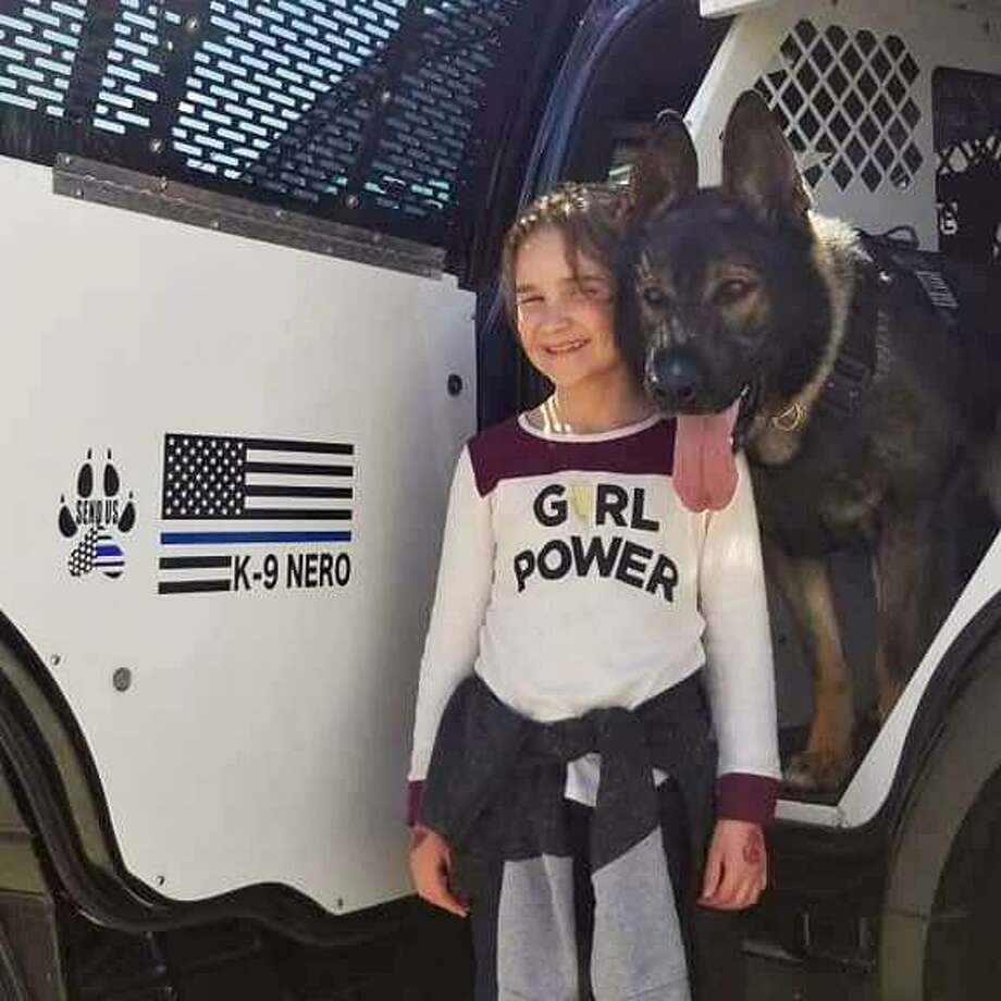 Mia Phinney met Portland police Sgt. James Kelly and his canine officer Nero recently, giving them handmade dog chew toys. Photo: Contributed Photo