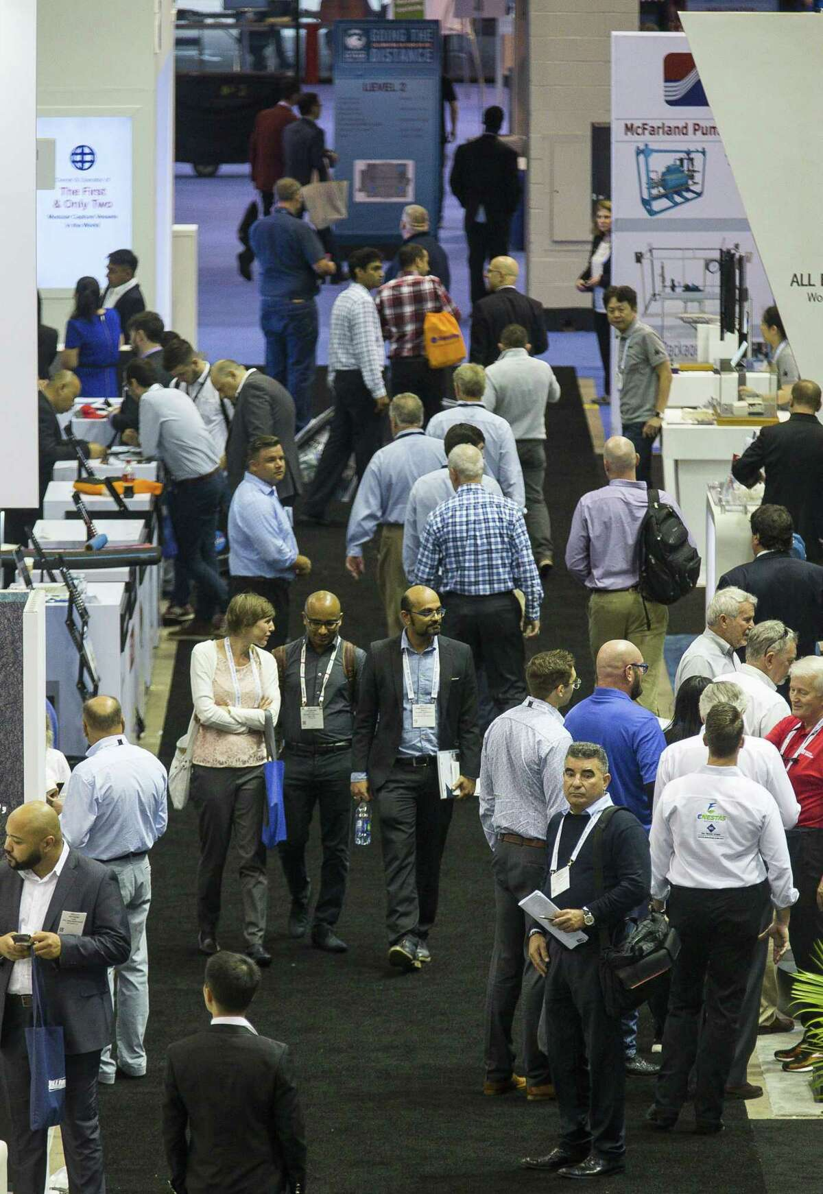 People walk through exhibits during the annual Offshore Technology Conference inside Houston's NRG Arena, Tuesday, May 7, 2019. Attendance fell this year to 59,200, the fifth consecutive year of participation decline. >>>See scenes from this year's conference ...