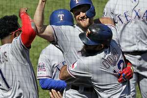 Texas Rangers' Hunter Pence, center, celebrates with Rougned Odor (12) and Elvis Andrus (1) as he returns to the dugout after hitting a grand slam off Pittsburgh Pirates relief pitcher Michael Feliz during the eighth inning of a baseball game in Pittsburgh, Wednesday, May 8, 2019. The Rangers won 9-6.(AP Photo/Gene J. Puskar)