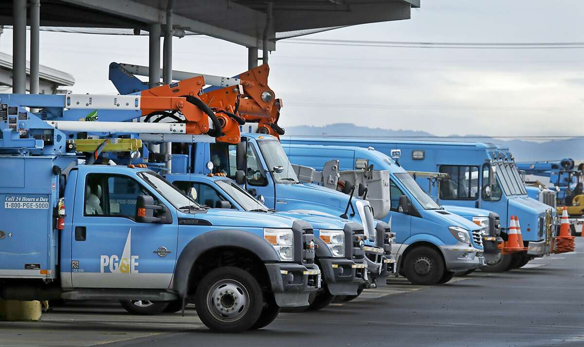 FILE - This Jan. 14, 2019, file photo shows Pacific Gas & Electric vehicles parked at the PG&E Oakland Service Center in Oakland, Calif. Pacific Gas & Electric Corp.'s top financial executives say they still haven't determined when the utility can start compensating victims of recent wildfires started by the utility's equipment. (AP Photo/Ben Margot, File)