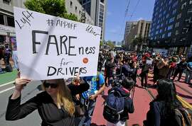 Lyft driver Erica Mighetto, of Sacramento, Calif., holds up a sign as protesters block Market Street outside of Uber headquarters Wednesday, May 8, 2019, in San Francisco. Some drivers for ride-hailing giants Uber and Lyft turned off their apps to protest what they say are declining wages as both companies rake in billions of dollars from investors. Demonstrations in 10 U.S. cities took place Wednesday, including New York, Chicago, Los Angeles, San Francisco and Washington, D.C. The protests take place just before Uber becomes a publicly traded company Friday. (AP Photo/Eric Risberg)