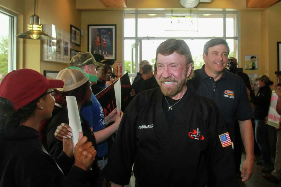 Chuck Norris, left, and Raising Cane's CEO Todd Graves, are greeted by employees when they enter the Raising Cane's in Missouri City where Graves presented a donation to Chuck and his Kickstart Kids charity. Photo: Gary Fountain, Contributor / © 2019 Gary Fountain