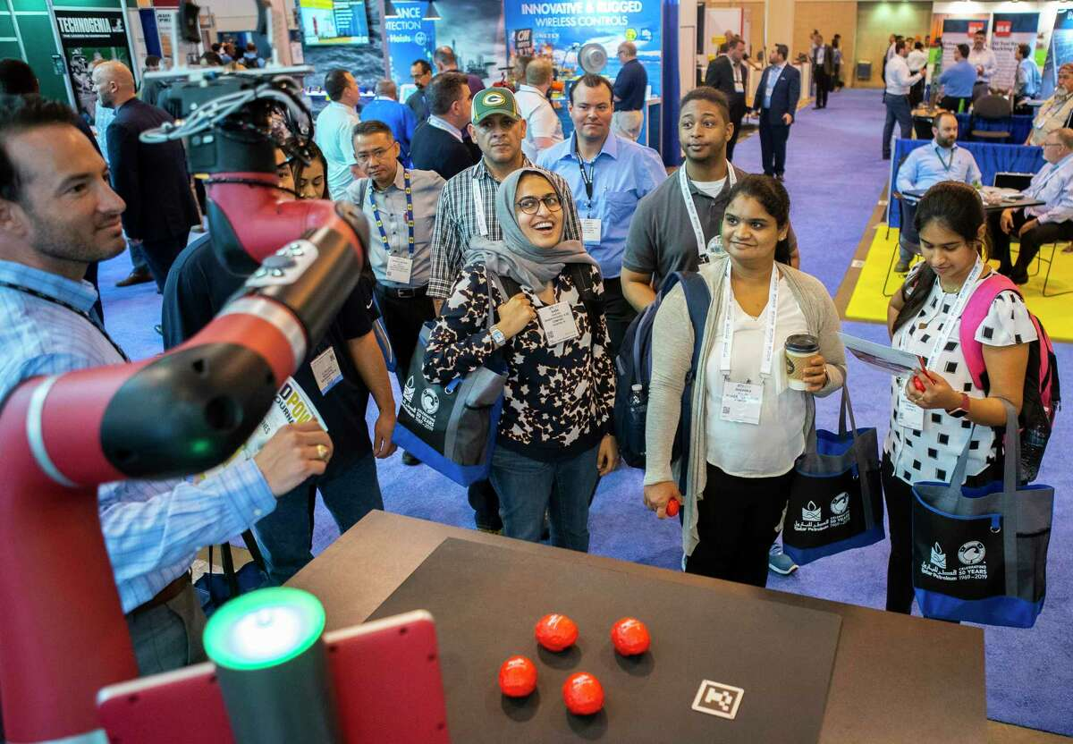 Attendees are handed branded stress balls from a robot named Sawyer, created by Rethink Robotics, during the annual Offshore Technology Conference inside Houston's NRG Center, Tuesday, May 7, 2019.