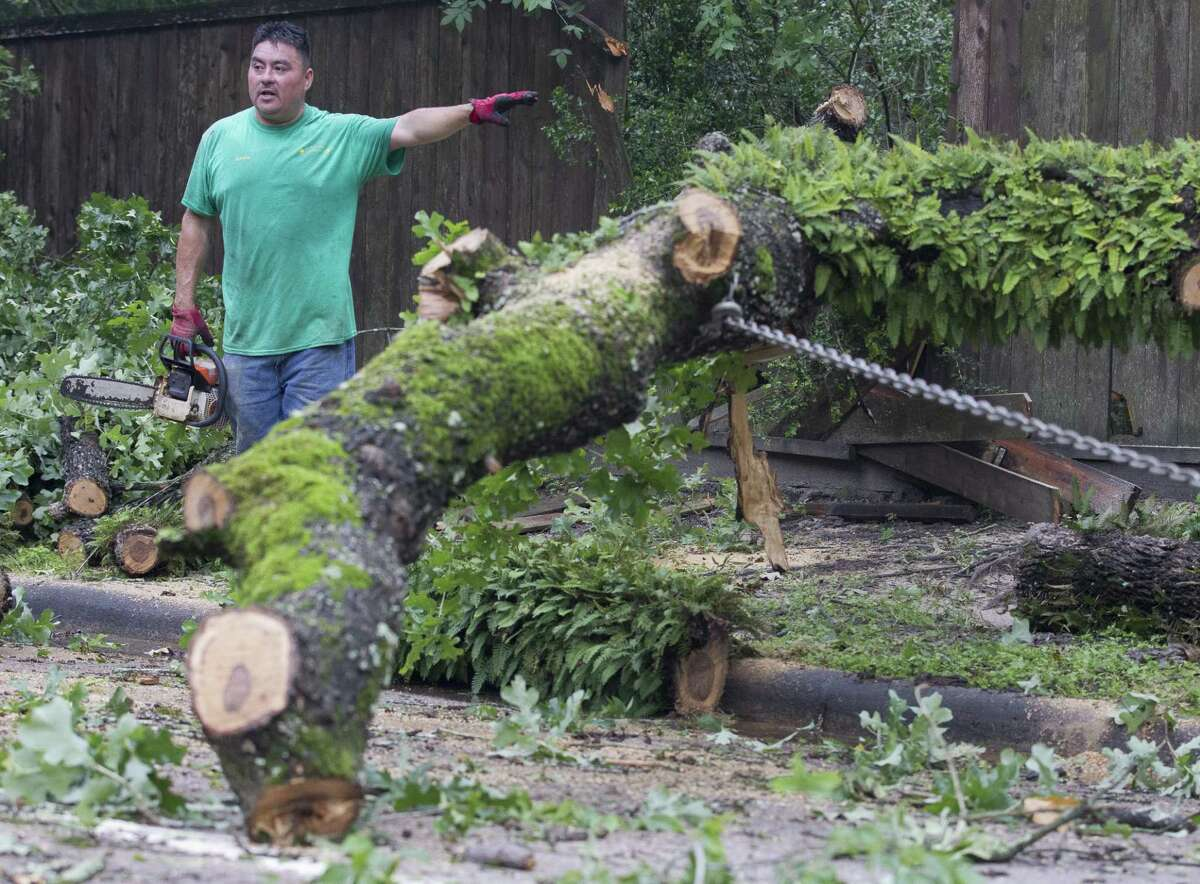Serafin Maldonado help clear a tree that blocked Kingwood Drive east of Woodlands Hills Drive, Wednesday, May 8, 2019, in Kingwood. Heavy rain battered parts of southeast Texas prompting flash flood warnings, power outages and calls for water rescues.
