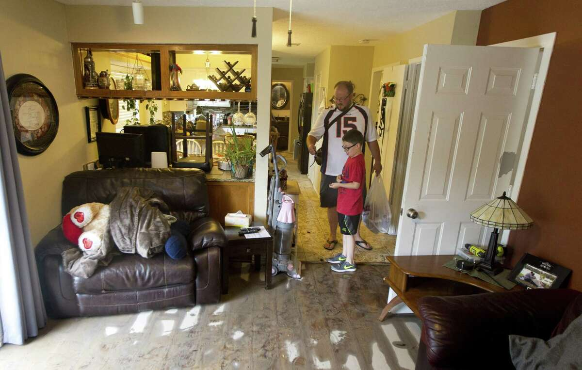 Michael Jordan talks with his son Tyler as they move belongings out of their flooded home in the Sherwood Trail subdivision, Wednesday, May 8, 2019, in Kingwood. Heavy rain battered parts of southeast Texas prompting flash flood warnings, power outages and calls for water rescues.