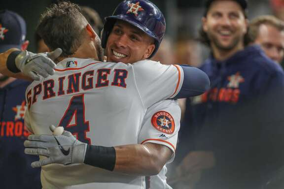 Houston Astros center fielder George Springer (4) hugs Houston Astros left fielder Michael Brantley (23) after he hit his second home run during an MLB baseball game at Minute Maid Park Wednesday, May 8, 2019, in Houston.