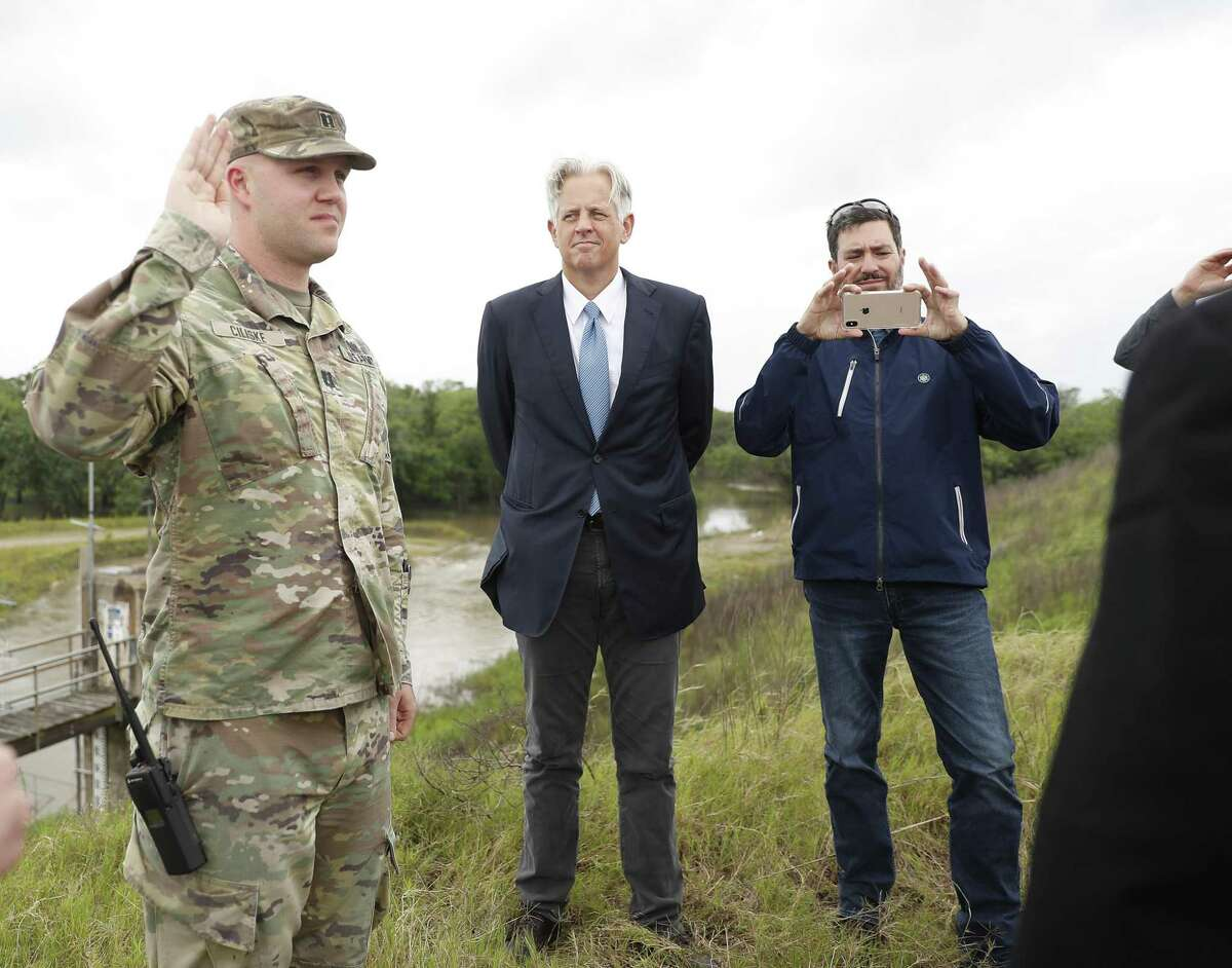 Captain Charles Ciliske with the US Army Corps of Engineers is swarn in by U.S. Judge Charles Lettow on the top of Barker Reservoir as the homeowners suing after Harvey went out to view homes in the Addicks and Barker Dam areas, in Houston, Wednesday, May 8, 2019.